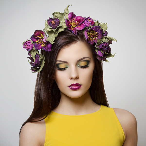 beautiful young woman with bright makeup wearing floral headband